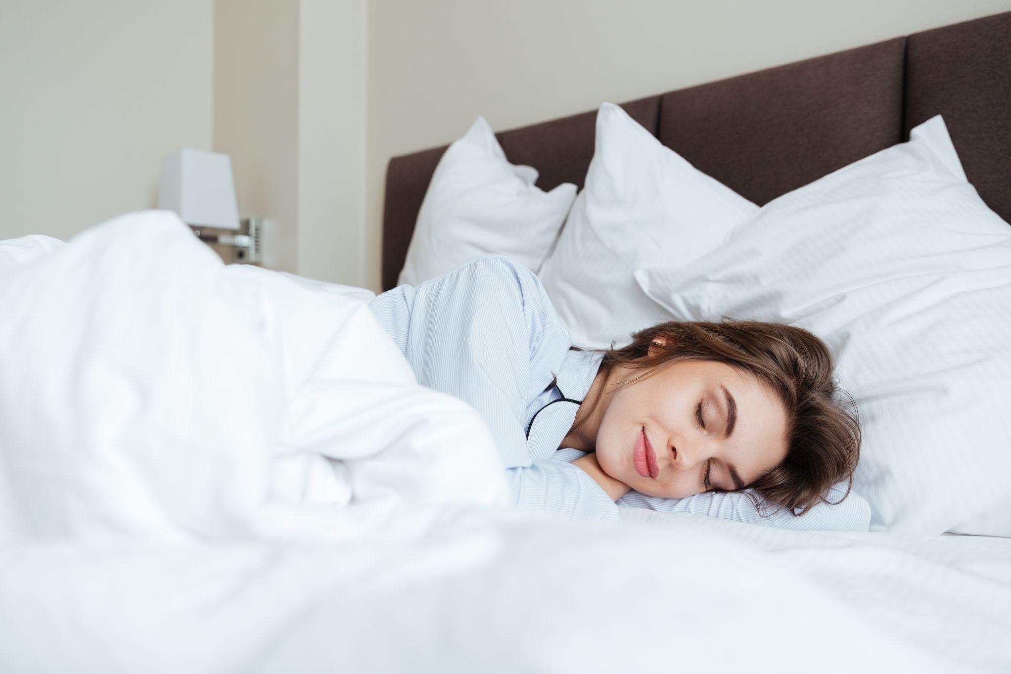 Ágyban fekvő nő ergonomikus párnán alszik