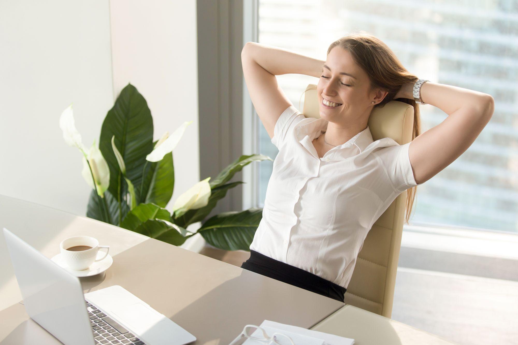 Boldog nő ergonomikus irodai széken ül