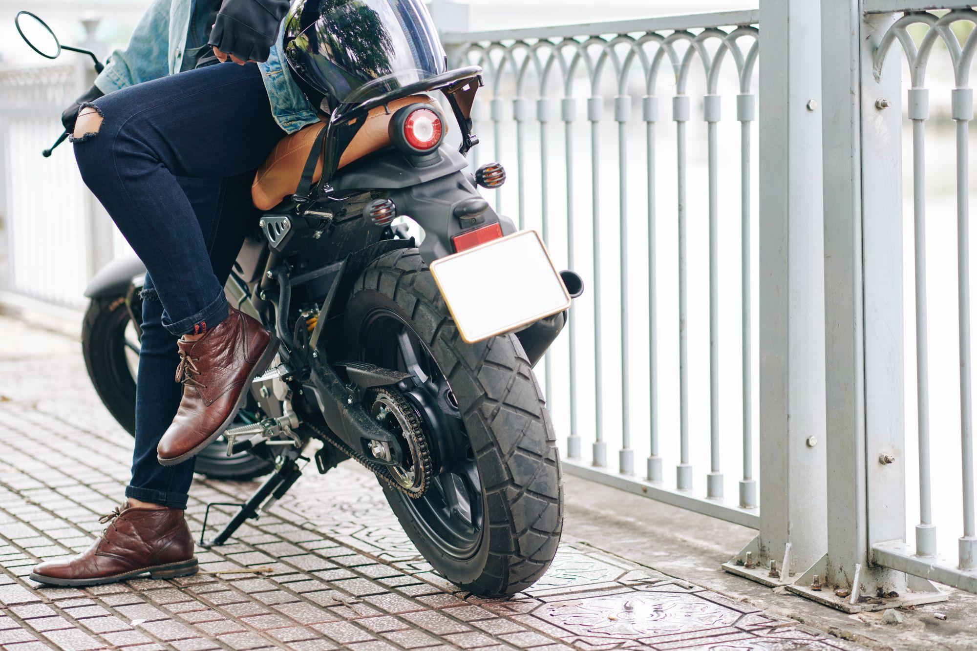 Bőrből készült rövid szárú motoros csizmát viselő férfi ül a motorján