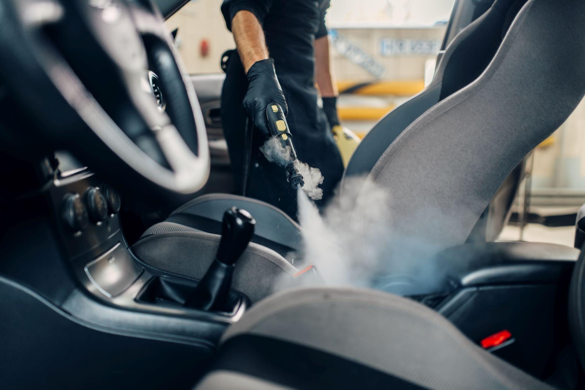 Egy férfi kézi gőztisztítóval autót takarít