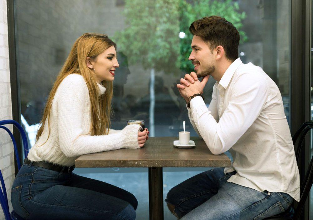 Férfi és nő asztalnál ülve beszélgetnek