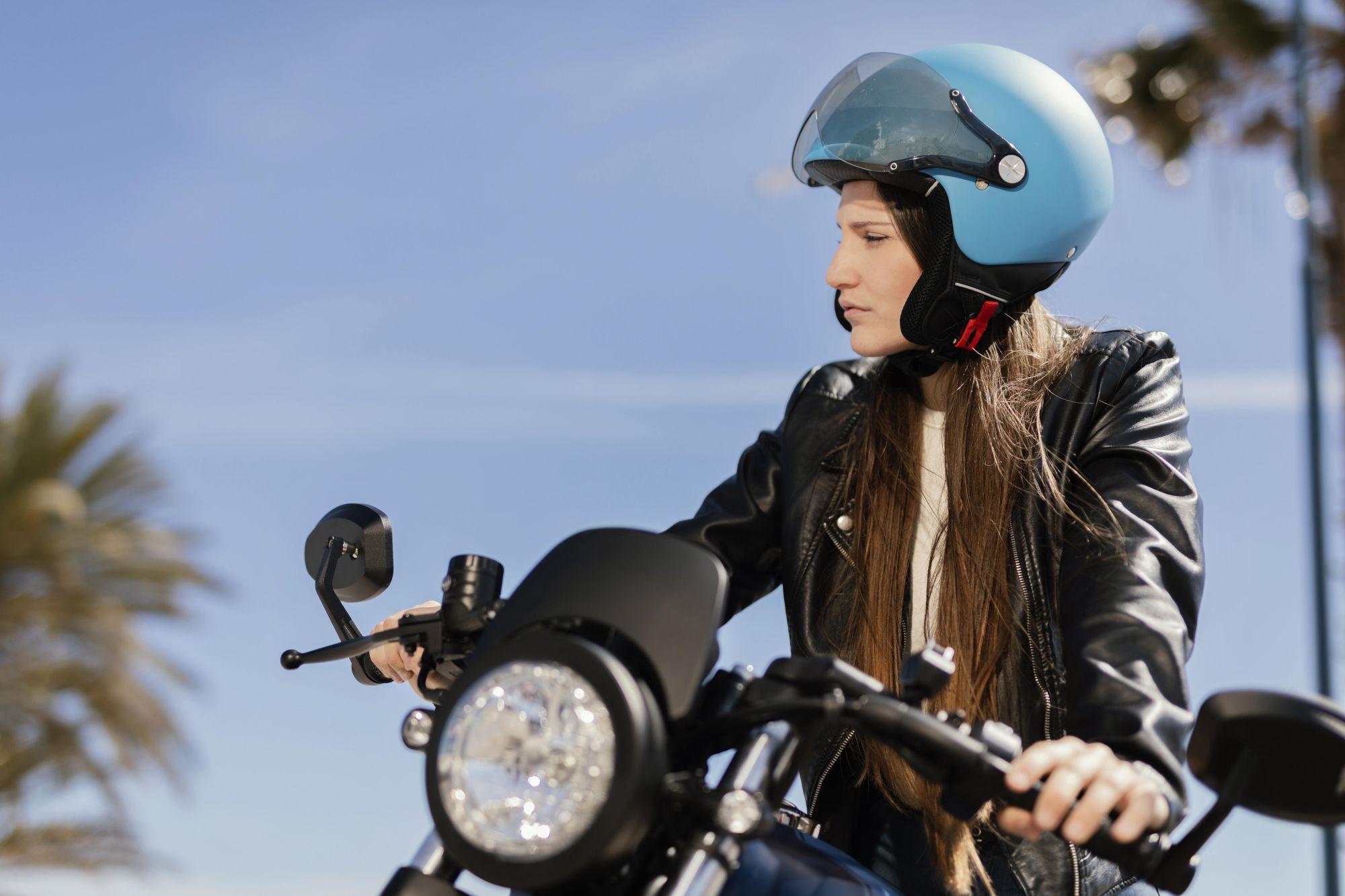 Fiatal lány motoron kék színű nyitott arcrészes bukósisakban