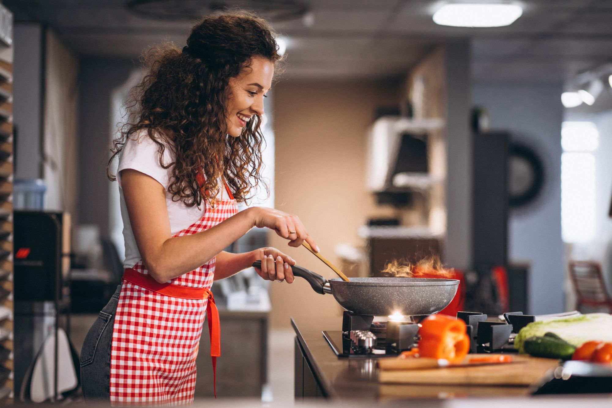 Gáztűzhelyen főző vidám nő