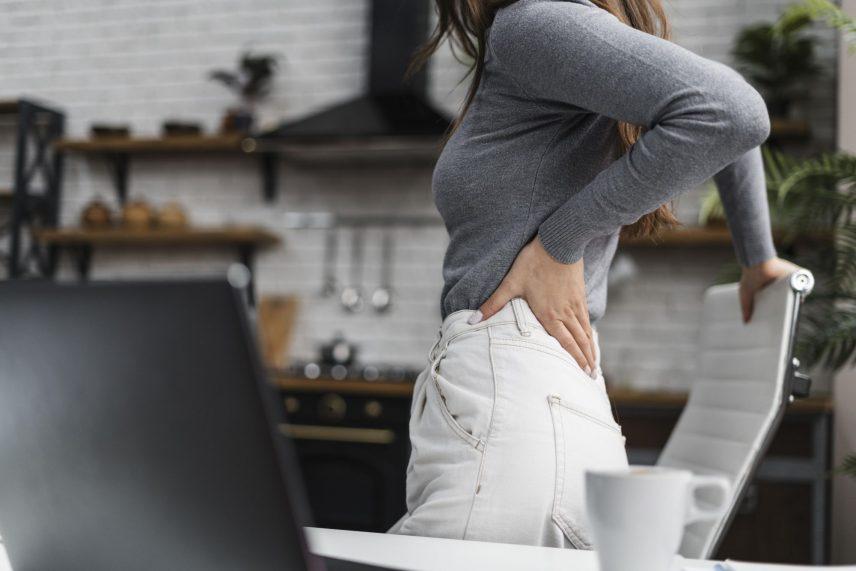 Hátfájással küzdő nő áll az íróasztal mellett