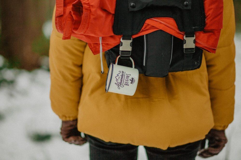 Túrázó hátizsákja, fém bögrével
