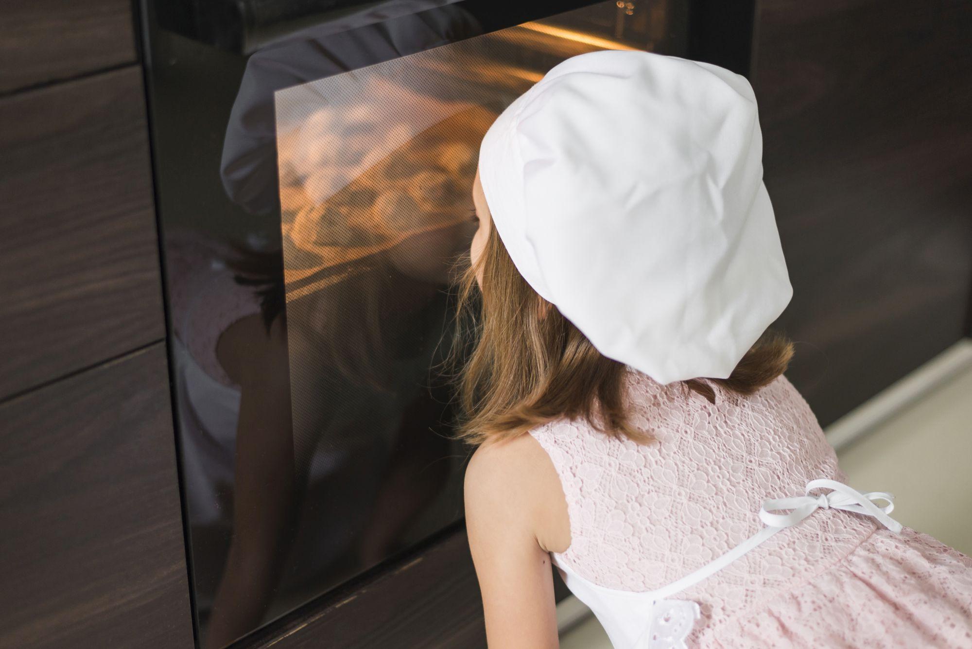 Kislány a gőzsütő előtt ülve nézi a megvilágított sütőteret