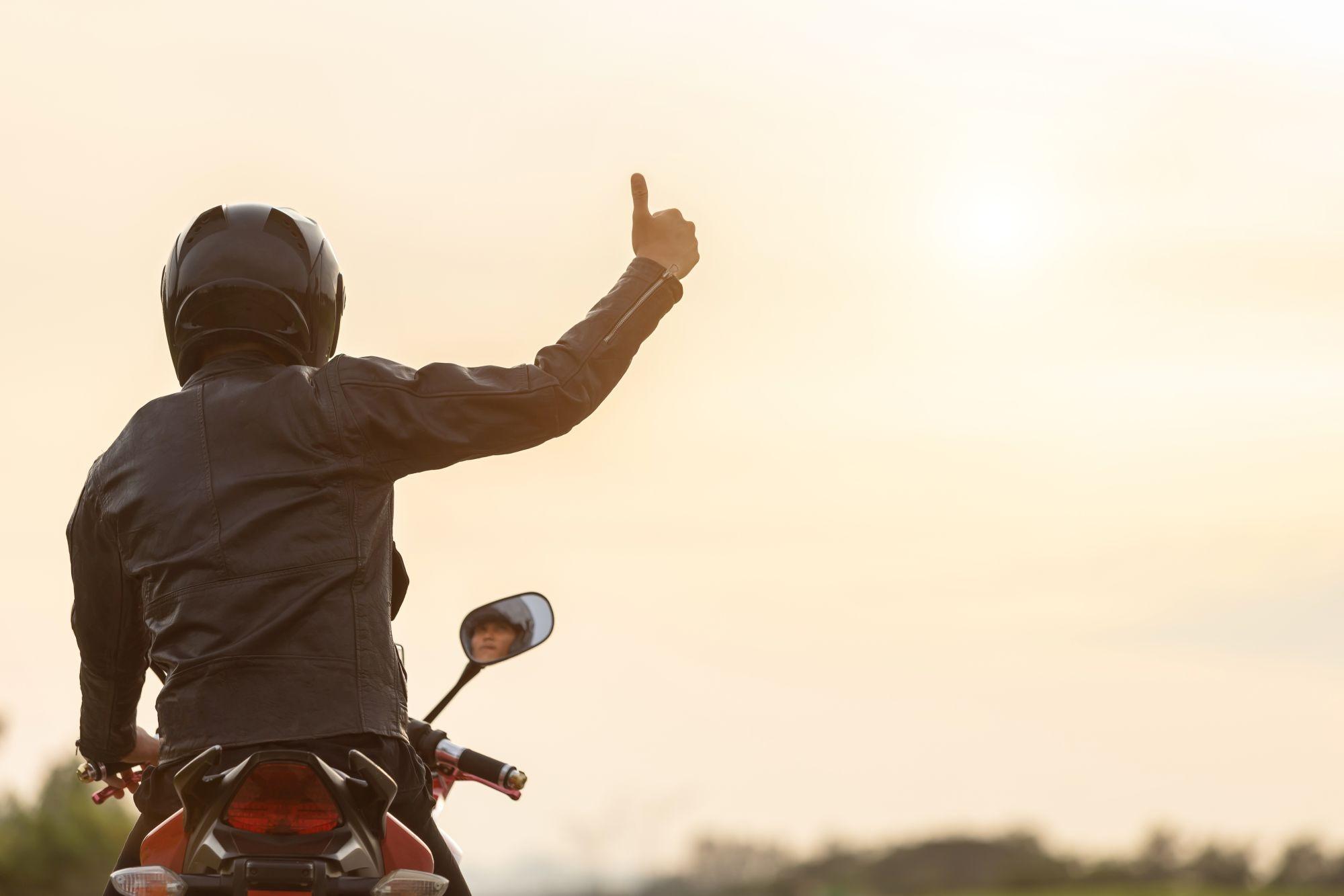 Motorozó nő hátulról motoros kabátban