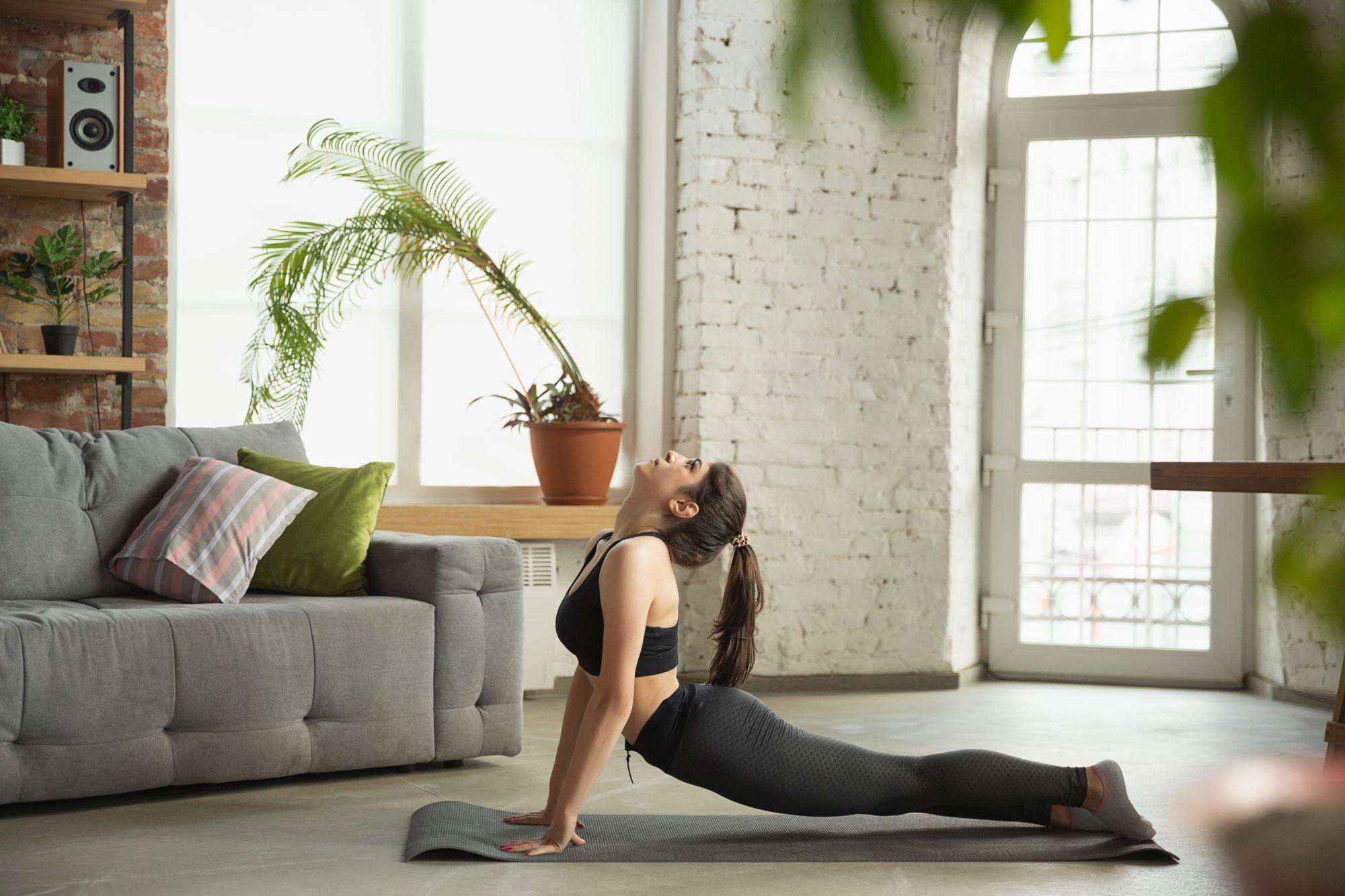 Nő nappaliban jógázik jógamatracon