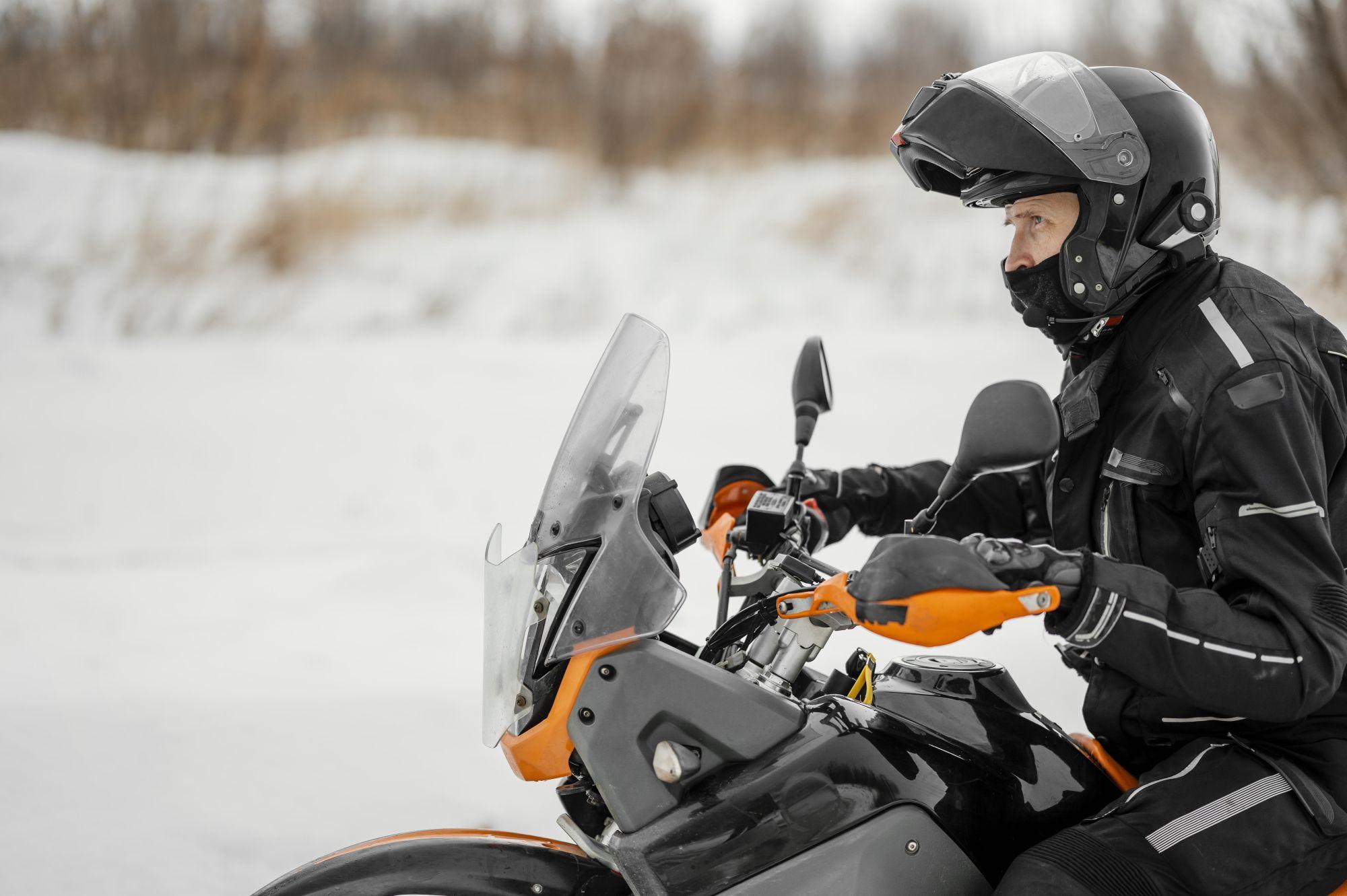 Nyitott állrészes bukósisakot viselő motorozó férfi fekete motoros ruhában