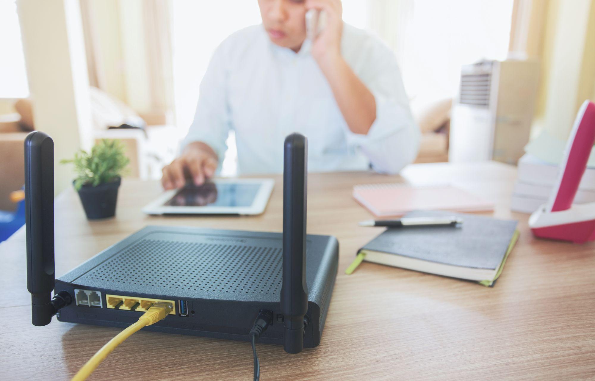 router a háttérben telefonáló férfivel