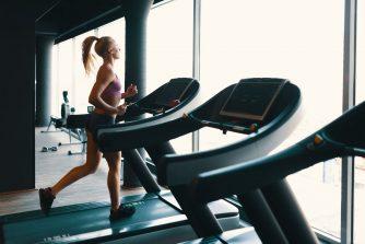 Sportos nő futópadot használ a kondiban