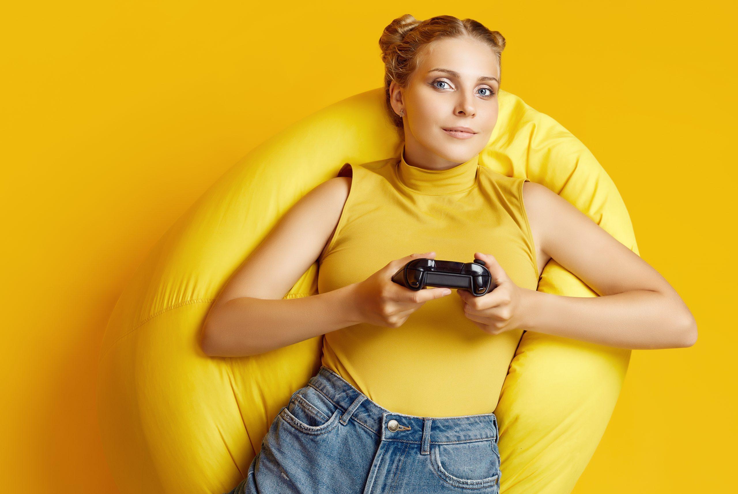 Vidám lány gamer széken fotelen játszik