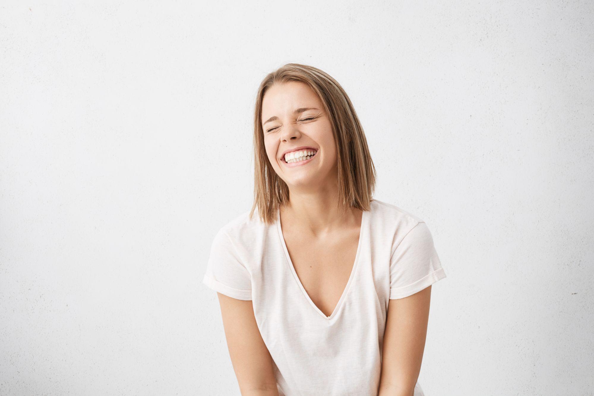 Vidám nő, aki Ultra Blanc fogkrémmel mosott fogat